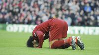 Penyerang Liverpool, Mohamed Salah, melakukan selebrasi sujud syukur usai membobol gawang AFC Bournemouth pada laga Premier League di Stadion Anfield, Sabtu (9/2). Liverpool menang 3-0 atas AFC Bournemouth. (AP/Rui Vieira)