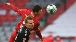 Bek Freiburg, Philipp Leinhart (depan) berebut bola dengan bek Bayern Munich, Benjamin Pavard dalam laga lanjutan Liga Jerman 2020/21 pekan ke-16 di Allianz Arena, Minggu (17/1/2021). Freiburg kalah 1-2 dari Bayern Munich. (AFP/Christof Stache/Pool)