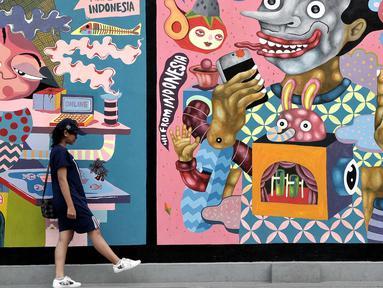 Pengunjung melintas di depan mural karya seniman Yogyakarta yang bertajuk INDONESIA IS GREAT  di museum Galeri Nasional, Jakarta, Sabtu (22/7). Pameran Mural tersebut merupakan agenda rutin museum Galeri Nasional. (Liputan6.com/Helmi Afandi)