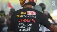 """Seorang warga mengenakan kaus yang bertuliskan """"Lawan Intoleransi, Radikalisme dan Terorisme"""" saat akan menghadiri Rembuk Nasional Aktivis 98 di JIExpo Kemayoran, Jakarta, Jakarta, Sabtu (7/7). (Merdeka.com/Imam Buhori)"""