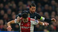 Pemain Ajax Dusan Tadic berebut bola dengan bek Real Madrid, Sergio Ramos pada leg pertama 16 besar Liga Champions di Johan Cruijff ArenA, Amsterdam, Rabu (13/2). Real Madrid harus bersusah payah menaklukkan Ajax dengan skor tipis 2-1. (AP/Peter Dejong)