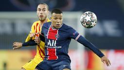 Striker Paris Saint-Germain, Kylian Mbappe, berebut bola dengan pemain Barcelona, Oscar Mingueza, pada laga Liga Champions di Stadion Parc des Princes, Kamis (11/3/2021). Kedua tim bermain imbang 1-1. (AP/Christophe Ena)
