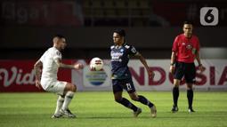 Pemain Persib Bandung Frets Butuan (tengah) mengontrol bola dibayangi pemain PS Sleman Aaron Michael Evans (kiri) dalam pertandingan semifinal leg kedua Piala Menpora 2021 di Stadion Manahan, Solo, Senin (19/4/2021). (Bola.com/Ikhwan Yanuar)
