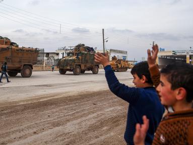 Sejumlah anak-anak melambaikan tangan ke iring-iringan pasukan lapis baja Turki (APC) yang melewati persimpangan perbatasan Bab al-Salamah antara Suriah dan Turki di utara provinsi Aleppo (21/1). (AFP/ Nazeer al-Khatib)