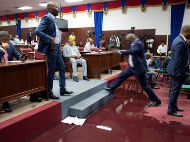 Seorang anggota parlemen melangkahi genangan air hujan pada lantai Gedung Parlemen Haiti di Port-au-Prince, Haiti, Rabu (21/8/2019). Bocornya atap pada Gedung Parlemen Haiti menyebabkan air masuk dan membasahi lantai. (AP Photo/Dieu Nalio Chery)