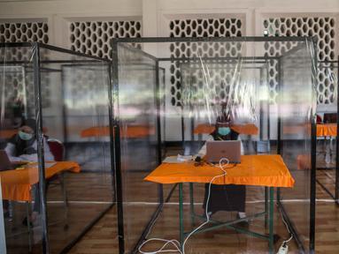 """Peserta dengan hasil """"rapid test"""" reaktif mengikuti ujian Seleksi Kompetensi Bidang (SKB) di bilik khusus di Surabaya, Selasa (22/9/2020). Badan Kepegawaian Daerah (BKD) Kota Surabaya menggelar ujian SKB yang diikuti 1.142 peserta CPNS dengan protokol COVID-19 secara ketat. (Juni Kriswanto/AFP)"""
