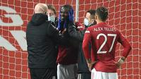 Bek Manchester United, Eric Bailly (tengah) mendapat penanganan tim medis usai terlibat benturan dengan pemain Watford dalam laga babak ke-3 Piala FA 2020/21 di Old Trafford, Sabtu (9/1/2021). Manchester United menang 1-0 atas Watford. (AFP/Oli Scarff/Pool)