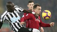 Gelandang Liverpool, Xherdan Shaqiri, berusaha melewati bek Newcastle, Mohamed Diame, pada laga Premier League di Stadion Anfield, Liverpool, Rabu (26/12). Liverpool menang 4-0 atas Newcastle. (AP/Jon Super)