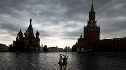 Orang-orang menutupi diri mereka dengan kantong plastik saat hujan di Lapangan Merah di Moskow, Rusia, 7 Juli 2020. Cuaca panas di Moskow terus berlanjut, dengan suhu diperkirakan mencapai lebih dari 30 derajat Celcius. (AP Photo/Pavel Golovkin)