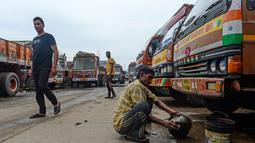 Seorang sopir mencuci di samping sebuah truk yang diparkir di sebuah terminal di Chennai (19/9/2019). Akibat pemogokan layanan transportasi, beberapa sekolah di ibukota nasional akan diliburkan saat pemogokan satu hari tersebut. (AFP Photo/Arun Sankar)