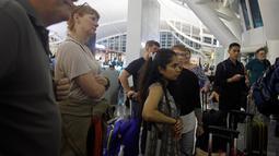 Sejumlah penumpang mencari informasi jadwal penerbangan di Bandara Ngurah Rai, Bali, Jumat (29/6). PT Angkasa Pura I menutup sementara operasional bandara selama 16 jam dikarenakan dampak abu vulkanik Gunung Agung. (AP/Firdia Lisnawati)