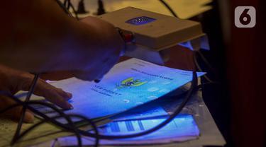 Petugas mengecek barang bukti sertifikat saat rilis kasus sindikat mafia tanah di Jakarta, Rabu (12/2/2020). Subdit II Harda Ditreskrimum Polda Metro Jaya bersama Kementerian ATR/BPN mengungkap sindikat mafia tanah menggunakan sertifikat palsu dan KTP elektronik ilegal. (merdeka.com/Imam Buhori)