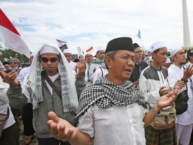 Massa berdoa bersama saat aksi Reuni 212 di kawasan Monas, Jakarta, Sabtu (2/12). Aksi yang diselenggarakan sebagai bentuk reuni kegiatan 2 Desember 2016 itu diisi dengan pembacaan zikir, salawat serta salat berjamaah. (Liputan6.com/Herman Zakharia)