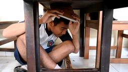Seorang siswa berlindung di bawah meja saat mengikuti simulasi gempa bumi dan tsunami di Jimbaran, Bali (5/11/2019). Latihan dilakukan untuk memberikan pengajaran kepada siswa agar mengantisipasi bahaya bencana gempa bumi dan tsunami yang bisa datang sewaktu-waktu. (AFP Photo/Sonny Tumbelaka)