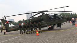 Tim penerbang berada di sisi helikopter Apache yang dipamerkan pada pameran Alat Utama Sistem Persenjataan TNI di Kawasan Monas, Jakarta, Kamis (27/9). TNI memiliki delapan helikopter Apache AH 64E buatan Amerika Serikat. (Liputan6.com/Helmi Fithriansyah)