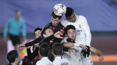 Para pemain Real Madrid dan Real Sociedad melompat berebut bola saat pertandingan lanjutan La Liga Spanyol di stadion Alfredo di Stefano di Madrid, Spanyol, Selasa (2/3/2021). Real Madrid bermain imbang atas Real Sociedad 1-1. (AP Photo/Bernat Armangue)