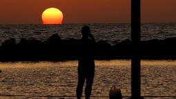 Seorang warga menyaksikan matahari terbenam di kota pesisir Mediterania Israel Netanya, utara Tel Aviv (8/6/2021). Kota ini memiliki penduduk sebanyak 173.300. (AFP/ Jack Guez)