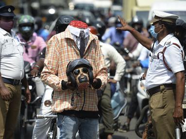 Petugas polisi bersama seorang sukarelawan (tengah) berpakaian seperti pengendara sepeda motor yang memegang kepala mockup dengan helm ambil bagian dalam kampanye kesadaran keselamatan jalan, di Chennai (7/7/2021). (AFP/Arun Sankar)