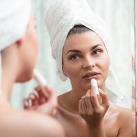 Ilustrasi mengoleskan lipbalm atau pelembap bibir. (iStockphoto)