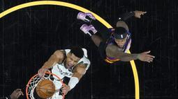 Sebelum quarter keempat, kedua tim bermain tidak terlalu agresif. Pemain bintang Bucks, Giannis Antetokounmpo (kiri bawah) hanya mampu mencetak 17 poin hingga penghujung quarter ketiga, ketika Phoenix Suns unggul 20 poin. (Foto: Getty Images via AFP/Pool/Matt York)