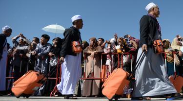 Jemaah calon haji berjalan menuju pesawat penerbangan khusus saat akan bertolak ke Tanah Suci Mekah di Bandara Provinsi Narathiwat, Thailand, Kamis (4/7/2019). Jutaan umat muslim dari penjuru dunia akan bertolak menuju Mekah untuk melangsungkan ibadah haji. (Madaree TOHLALA/AFP)
