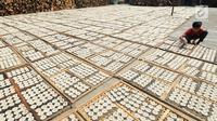 Pekerja mengeringkan kerupuk kaleng di industri UMKM Nineung di Pamulang, Tangsel, Banten, Jumat (21/6/2019). Kenaikan harga tepung tapioka yang mencapai lebih dari seratus persen semenjak beberapa bulan terakhir menyebabkan produsen kerupuk mengurangi kualitas kerupuk. (merdeka.com/Arie Basuki)