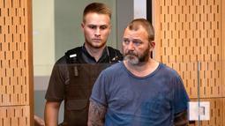 Terduga penyebar video serangan Masjid Al Noor, Philip Arps (kanan) menjalani persidangan di Pengadilan Distrik Christchurch, Selandia Baru, Rabu (20/3). Arps menghadiri dengan pengawalan ketat polisi. (Mark Mitchell/Pool Photo via AP)