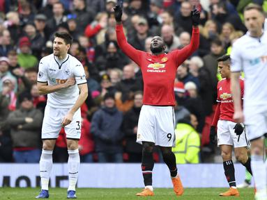 Pemain Manchester United, Romelu Lukaku (tengah) merayakan golnya ke gawang Swansea City pada laga Premier League di Old Trafford, (31/3/2018).  Manchester United menang 2-0. (Anthony Devlin/PA via AP)