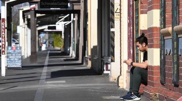 Seorang pekerja beristirahat di sebuah kafe yang biasanya ramai saat kota itu mengalami penguncian keenam saat memerangi wabah varian Delta dari coronavirus di Melbourne (25/8/2021). (AFP/William West)