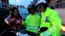 Kepolisian bekerjasama dengan Fullo mensosialisasikan larangan berhenti pada garis stop pada pengguna jalan diserta pembagian cokelat gratis pada pengendara yang tertib di kawasan Cideng, Jakarta, Senin (23/2). (Liputan6.com/Johan Tallo)