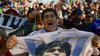Fans berkumpul di luar kamar jenazah tempat jasad mendiang legenda sepak bola Argentina Diego Maradona akan menjalani otopsi di San Fernando, Buenos Aires, Argentina, 25 November 2020. Jenazah Diego Maradona akan disemayamkan di Istana Presiden. (RONALDO SCHEMIDT/AFP)