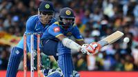 Pemain kriket Sri Lanka Niroshan Dickwella (kana) diawasi oleh wicketkeeper India Mahendra Singh Dhoni burusaha memukul bola dalam pertandingan kriket One Day International (ODI) di Dambulla (20/8). (AFP Photo/Lakruwan Wanniarachchi)