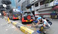 Warga, Polisi dan TNI mengambil peluru setelah kendaraan Polisi terbakar di Jalan Brigjen Katamso, Slipi, Jakarta, Rabu (22/5/2019). Belum diketahui penyebab terbakarnya dua bus yang terparkir bersama bus polisi lainnya dilokasi tersebut. (merdeka.com/Arie Basuki)