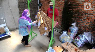 Pekerja menimbang sampah rumah tangga di bank sampah Gepe Two, Perumahan Griya Pamulang II, Tangerang Selatan, Banten, Rabu (23/12/2020). Bank sampah ini dikelola secara swadaya oleh masyarakat. (merdeka.com/Arie Basuki)