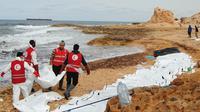 Petugas Bulan Sabit Merah Libya mengevakuasi jenazah para migran yang ditemukan terdampar di pantai utara Libya, Selasa (21/2). Sedikitnya 74 jenazah imigran tenggelam saat melintasi perairan Mediterania dalam upaya mencapai Eropa. (MOHANED KREMA/AFP)