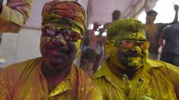 Umat Hindu merayakan Holi, festival warna musim semi, di sebuah kuil di desa Nandgaon, negara bagian Uttar Pradesh, 5 Maret 2020. Ribuan orang India menyambut musim semi pada Kamis (5/3) dengan merayakan Festival Holi yang identik dengan aksi saling melemparkan bubuk warna warni. (Money SHARMA/AFP)