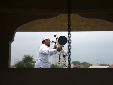 Petugas meneropong posisi hilal (bulan) dari Pondok Pesanteren Al-Hidayah Jakarta, Selasa (15/5). Pemantauan hilal ini dilakukan untuk menentukan jatuhnya 1 Ramadan 1439 H. (Merdeka.com/Imam Buhori)