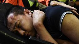 Tim medis membawa seorang pria yang diduga mata-mata China terluka setelah diikat oleh pemrotes pro-demokrasi saat unjuk rasa di bandara internasional Hong Kong (13/8/2019). Polisi anti huru hara bentrok dengan pengunjuk rasa pro-demokrasi di bandara Hong Kong Selasa malam. (AFP Photo/Anthony Wallac