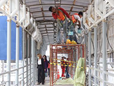 Pekerja mengecat jembatan penyeberangan orang di kawasan Senayan, Jakarta, Jumat (6/7). Pengecatan tersebut merupakan bagian dari proyek revitalisasi JPO guna meningkatnya kenyamanan pejalan kaki. (Liputan6.com/Immanuel Antonius)