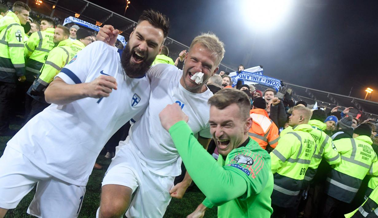 Pemain Finlandia Tim Sparv (kiri), Paulus Arajuuri (tengah), dan Lukas Hradecky (kanan) merayakan kemenangan mereka atas Liechtenstein pada babak kualifikasi Grup J Piala Eropa 2020 di Helsinki, Finlandia, Jumat (15/11/2019). Finlandia mencetak sejarah dengan lolos ke Piala Eropa. (Markku Ulander/Le