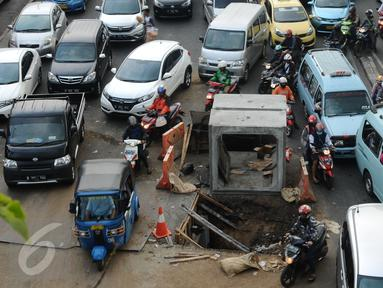 Pengendara motor menghindari lubang besar saluran air di perempatan Jalan Matraman Raya, Jakarta, Selasa (19/1/2016). Jalan Matraman Raya yang mengarah Kramat Raya macet parah imbas dari perbaikan saluran air. (Liputan6.com/Helmi Fithriansyah)