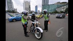 Mulai hari Minggu (18/1/2015), petugas kepolisian memberikan sanksi berupa denda senilai Rp 500 ribu bagi pemotor yang nekat melintasi Jalan MH Thamrin-Medan Merdeka Barat, Jakarta. (Liputan6.com/Miftahul Hayat)