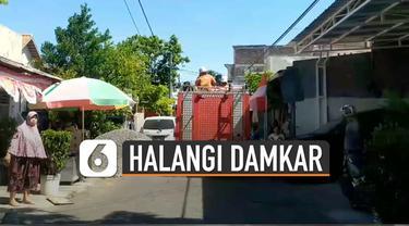 Petugas dan warga terpaksa bekerjasama mengangkat dan menggeser mobil tersebut untuk dimasukkan sementara ke garasi warga.