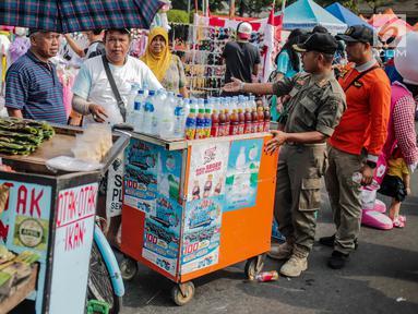 Petugas Satpol PP menertibkan PKL di kawasan car free day (CFD), Bundaran HI, Jakarta, Minggu (4/8/2019). Penertiban dilakukan karena keberadaan PKL membuat tidak nyaman pengunjung CFD yang ingin berolahraga, berorasi, atau sekadar jalan-jalan. (Liputan6.com/Faizal Fanani)