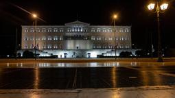 Pemandangan gedung parlemen dengan jalanan yang kosong di Athena, Yunani, Minggu (25/10/2020). Pemerintah Yunani telah memberlakukan jam malam di Athena, Thessaloniki, dan daerah lain dengan tingkat infeksi COVID-19 yang tinggi serta kewajiban penggunaan masker. (AP Photo/Yorgos Karahalis)