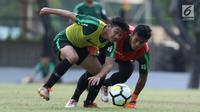 Pemain Indonesia U-19, Samuel Christianson (kiri) berebut bola dengan rekannya di Lapangan A Kompleks GBK, Jakarta, Rabu (3/10). Latihan ini persiapan penentuan skuat utama Timnas Indonesia di Piala Asia U-19. (Liputan6.com/Helmi Fithriansyah)
