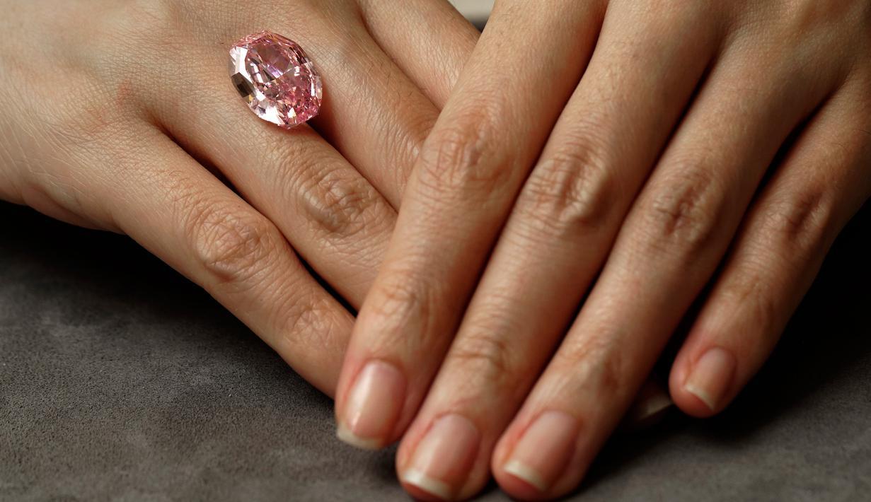 Model memperlihatkan berlian berwarna purple pink yang sangat langka di ruang lelang Sotheby Hong Kong pada 12 Oktober 2020. Berlian berbentuk oval yang ditemukan di pertambangan Rusia ini akan dilelang pada 11 November mendatang di Jenewa. (AP Photo/Vincent Yu)