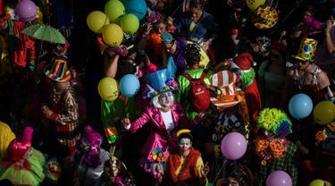 Orang-orang yang mengenakan pakaian badut ikut serta dalam parade badut tahunan di Sesimbra, Portugal pada Senin (4/3/2019). Perayaan ini dilakukan setiap tahun dan jatuh pada hari Senin. (PATRICIA DE MELO MOREIRA / AFP)