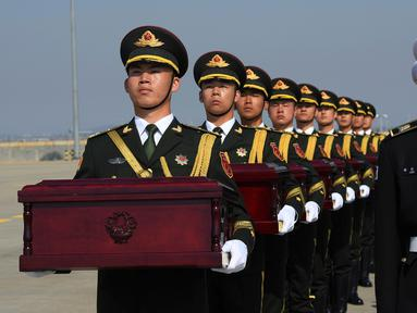 Tentara membawa peti mati berisi sisa-sisa tentara China yang menjadi korban dalam Perang Korea di Bandara Internasional Incheon, Seoul, Korea Selatan, Rabu (3/4). Sebanyak 10 tentara China yang tewas dalam Perang Korea 1950-53 dipulangkan dari Korea Selatan. (Jung Yeon-je/Pool Photo via AP)