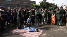 Pasukan keamanan mengeksekusi pria yang memperkosa dan membunuh gadis berusia empat tahun di alun-alun Tahrir, Ibu Kota Sanaa, Yaman (14/8). Warga berkumpul menyaksikan eksekusi pria bernama Hussein al-Saket 22 tahun tersebut. (AFP Photo/Mohammed Huwais)